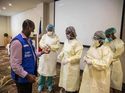 Haitian midwives participating in a dressing and undressing simulation session with personal protective equipment (PPE)